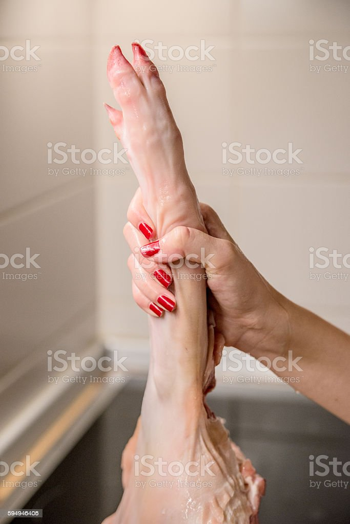 Woman holding raw pork leg in her kitchen stock photo