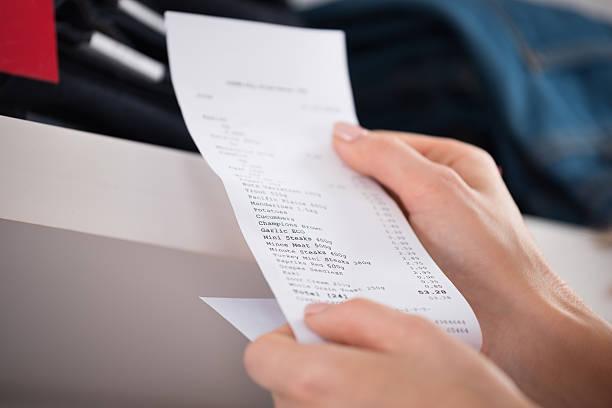 woman holding receipt in store - receipt stock photos and pictures