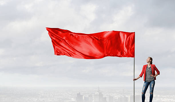 Woman holding red flag . Mixed media stock photo