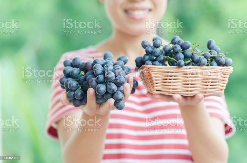 Frau mit roten Trauben in einem Korb – Foto