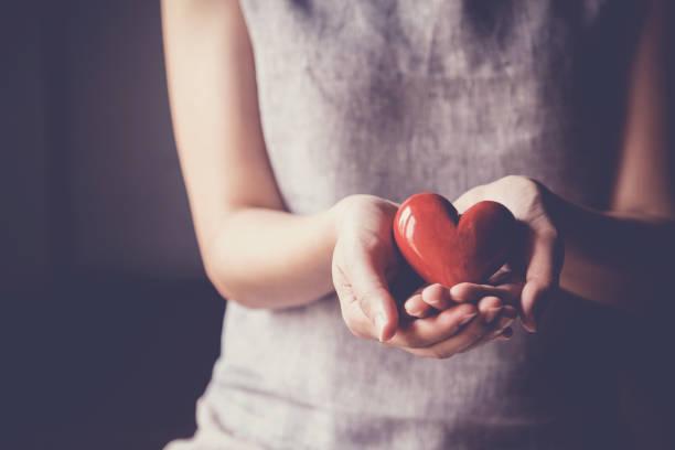 Frau mit rotem Herzen, Krankenversicherung, Spenden-Charity-Konzept – Foto