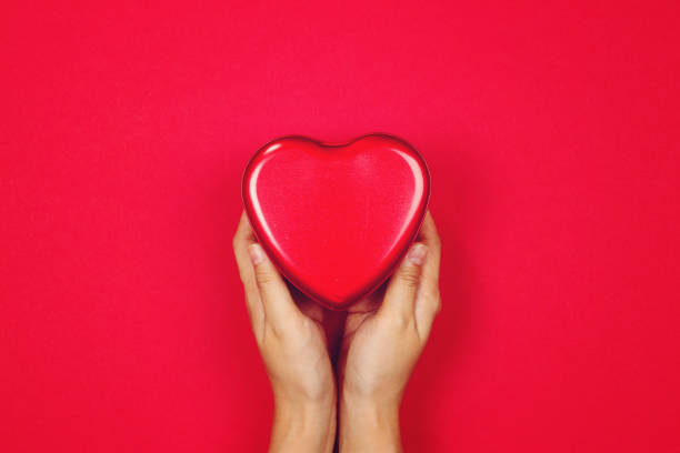woman holding red heart on red background - organ donation stock pictures, royalty-free photos & images