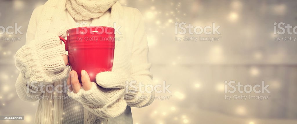 Woman holding red mug in snowy night stock photo