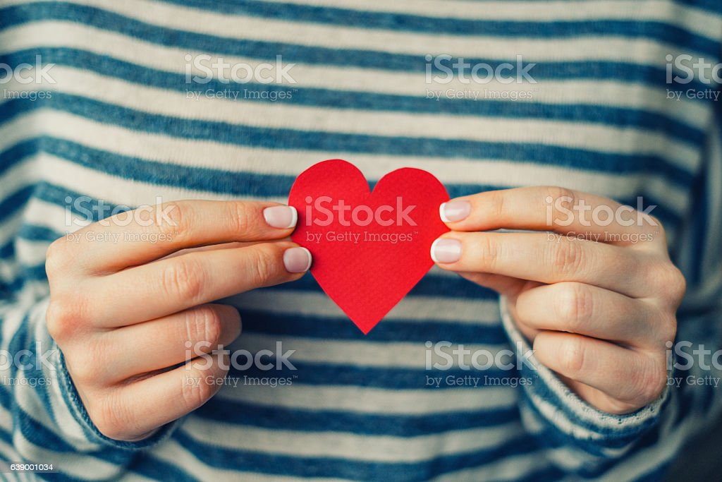 Woman holding red paper heart stock photo