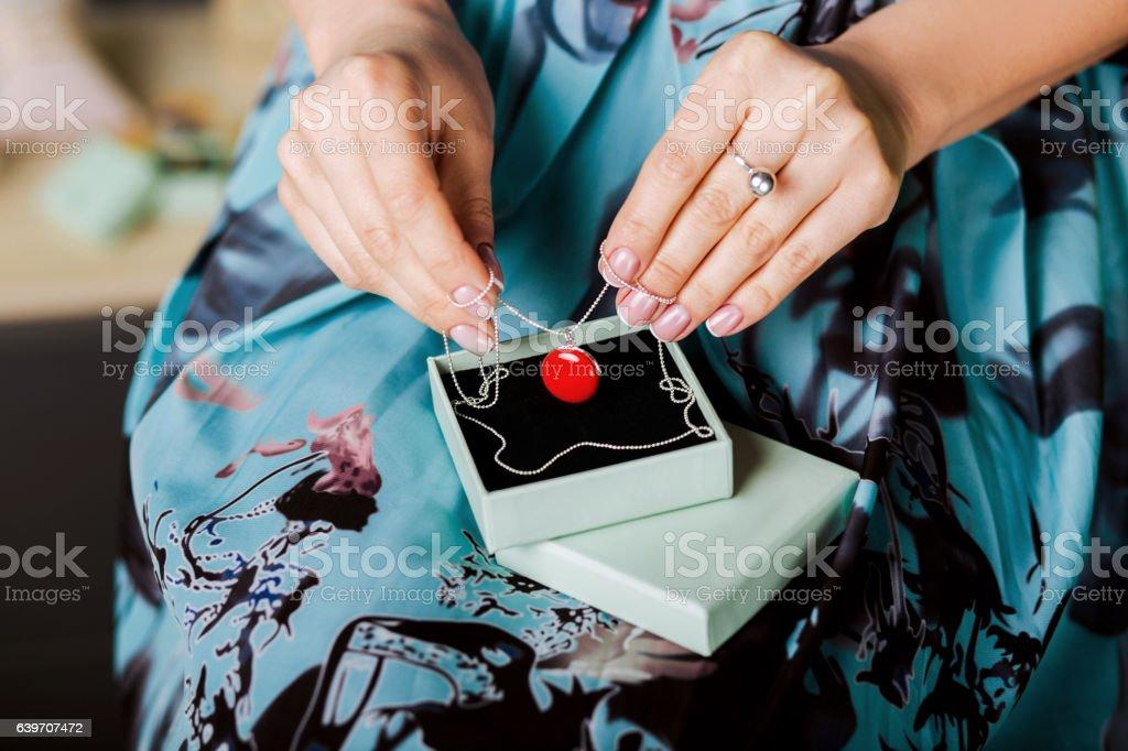 woman holding red pendant, closeup stock photo
