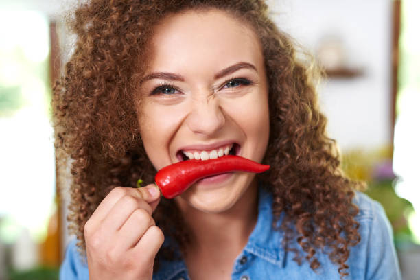 Woman holding red pepper in her mouth stock photo