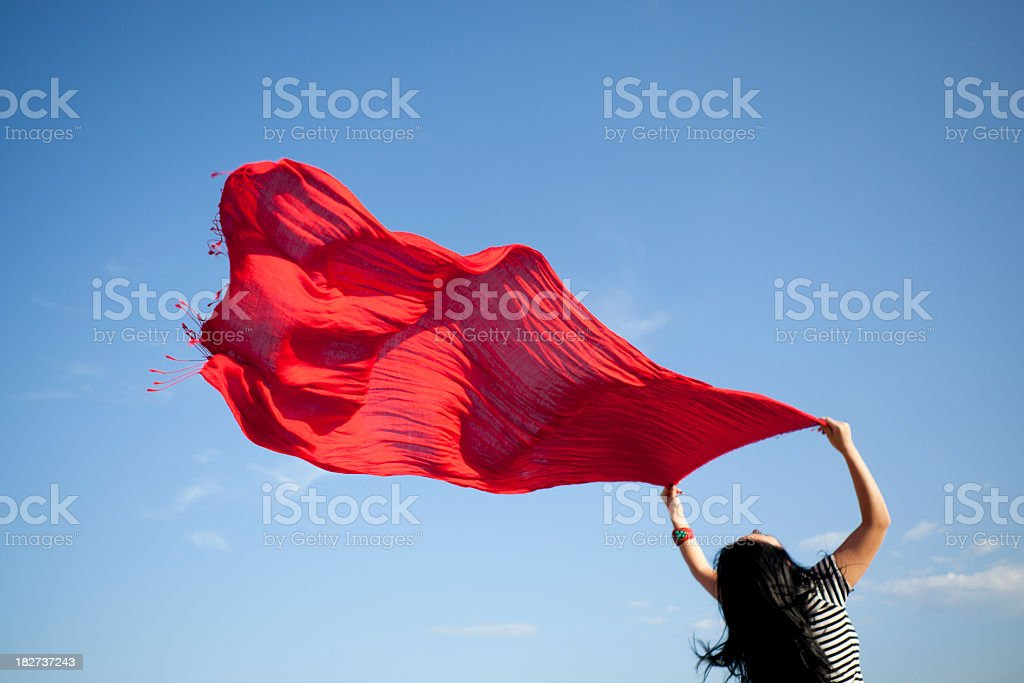 Woman Holding Red Shawl In The Wind On Blue Sky royalty-free stock photo