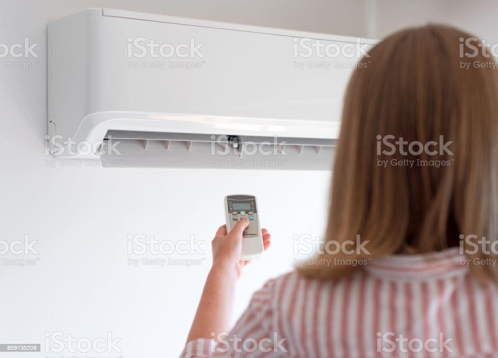 Frau mit Fernbedienung darauf abzielen, die Klimaanlage. – Foto