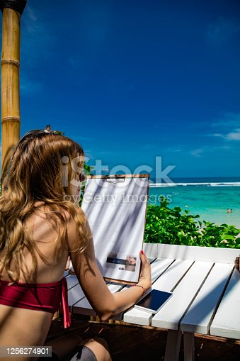 Woman holding restaurant food menu for ordering - tropical exotic view.