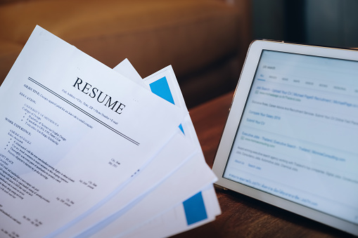 woman holding resume application with using tablet digital to job search on internet. applying for a job concept.
