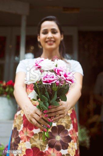Beautiful florist woman holding a bouquet of fresh rose flowers