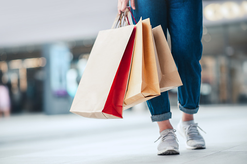 Closeup - Woman holding sale shopping bags. Consumerism, shopping, lifestyle concept
