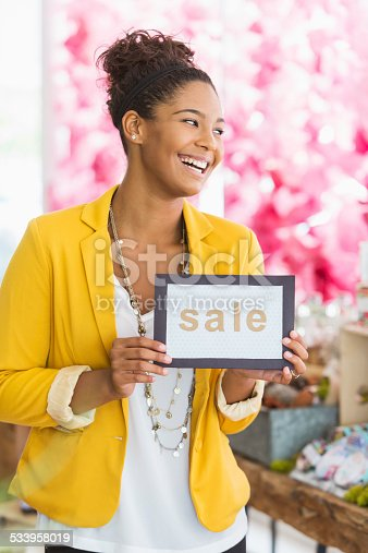 istock Woman holding SALE sign 533958019
