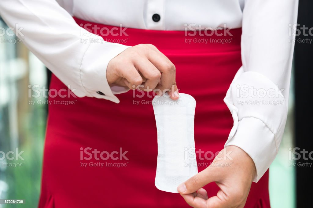 Woman holding sanitary napkins with red skirt - woman on her period. stock photo