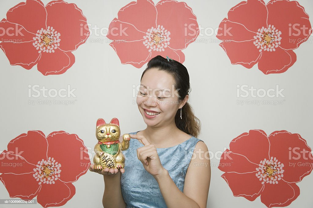 Woman holding sculpture of traditional fortune cat Maneki Neko foto de stock libre de derechos
