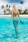 Beautiful blond female Tourist in Bikini holding a sea shell and snorkel in the clear turquoise water on a private island on the Maldives. Split shot. Nikon D850 with UW Case. Converted from RAW.
