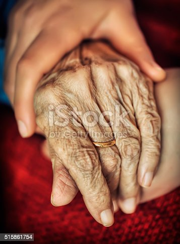499062115istockphoto Woman holding senior woman's hand 515861754