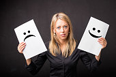 istock Woman holding sheets with sad and happy smileys 516929532