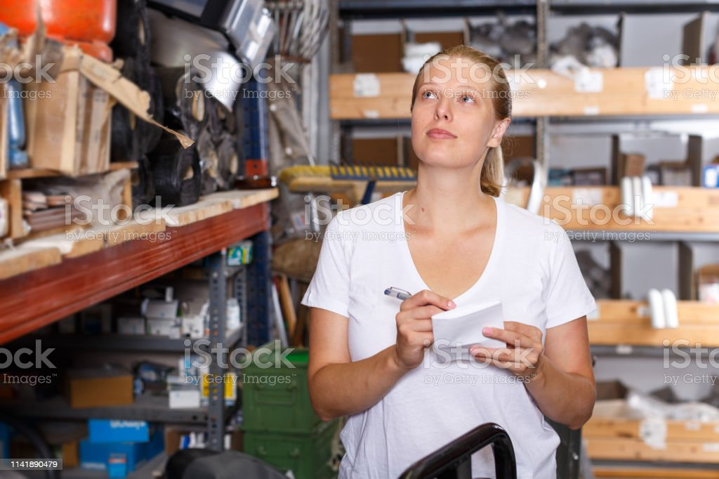 Young woman holding shop list and choosing tools at shelves in build...