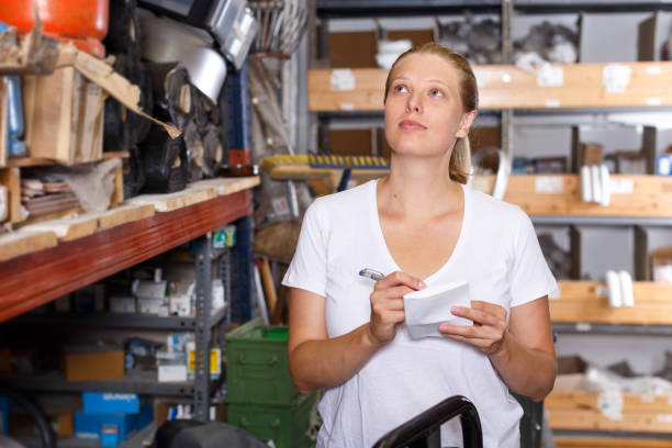 Woman holding shop list and choosing  tools at shelves in build store stock photo