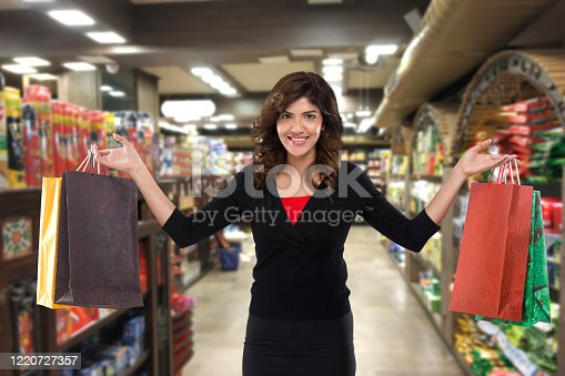 Excited woman holding shopping bags at grocery aisle of supermarket