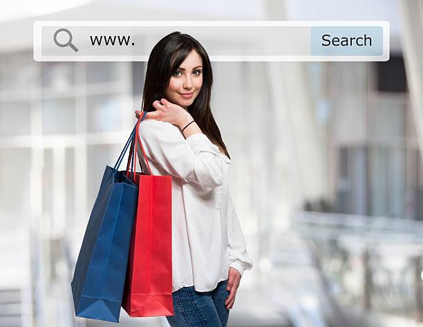 frau mit einkaufstüten vor einem suche bar - dresses online shop stock-fotos und bilder