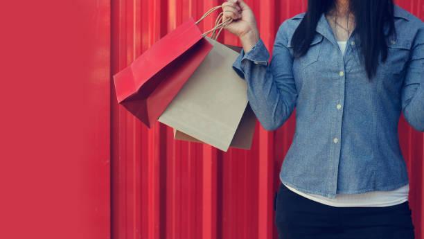 frau hält einkaufstaschen auf rotem hintergrund - heute ist freitag stock-fotos und bilder