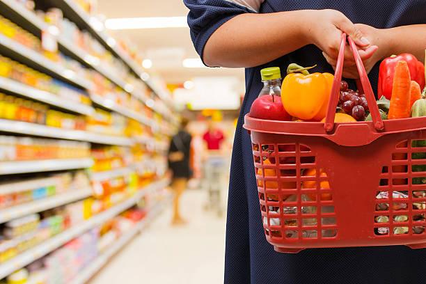 Mujer sosteniendo cesta de compras en el supermercado - foto de stock