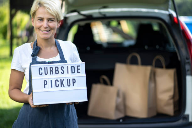 Woman holding sign curbside pick up MIddle age woman holding white sign curbside pickup curbsidepickup stock pictures, royalty-free photos & images