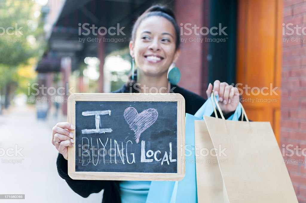 Woman holding sign that says I love buying local  stock photo