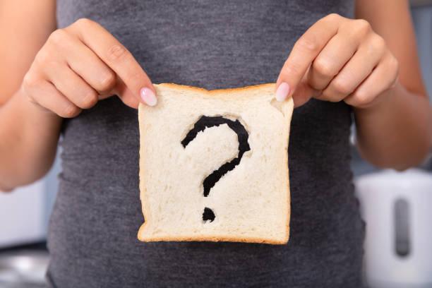 woman holding slice of bread with question mark sign - impasto per il pane foto e immagini stock