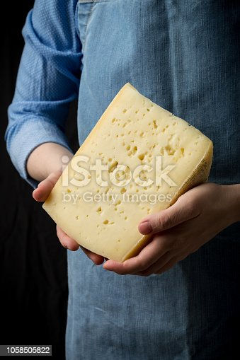 istock Woman holding slice of cheese wearing blue apron on dark background 1058505822