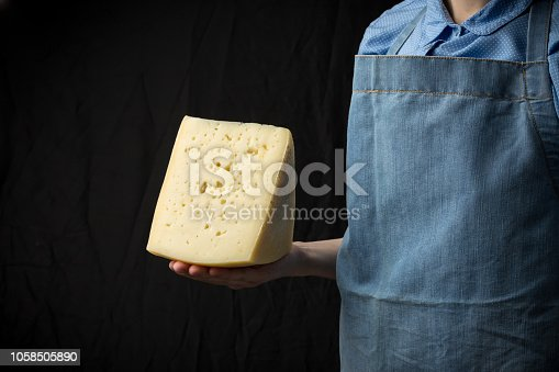 istock Woman holding slice of cheese wearing blue apron on dark background 1058505890
