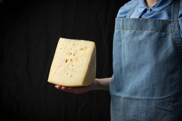 frau mit scheibe käse tragen blaue schürze auf dunklem hintergrund - teller kaufen stock-fotos und bilder