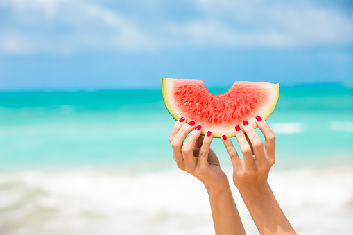 Woman holding slice of watermelon on the beach.
