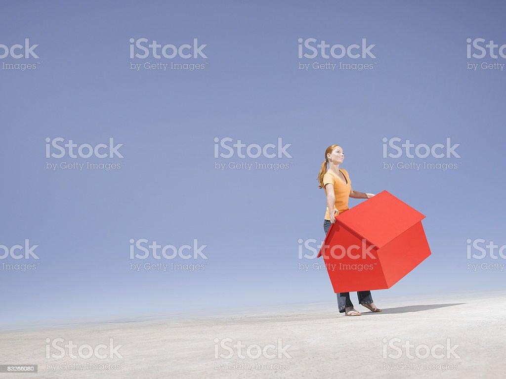 Frau hält kleine Modell Haus in der Wüste – Foto