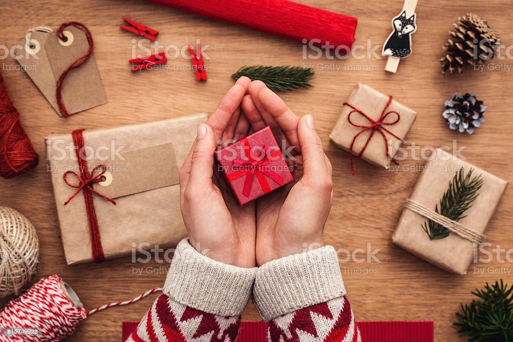 Woman holding small, red, christmas gift box over wooden desk stock photo