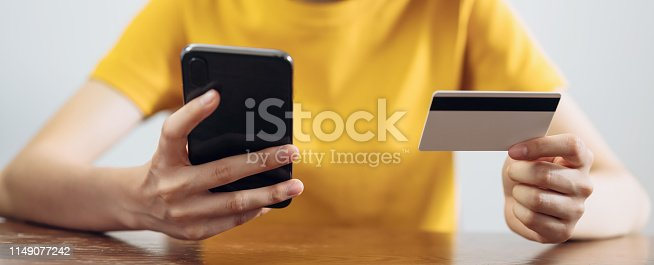istock woman holding smart phone and credit card with shopping online. proportion of the banner for ads. 1149077242
