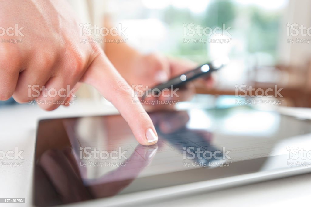 Woman Holding Smart Phone and Touching Digital tablet royalty-free stock photo