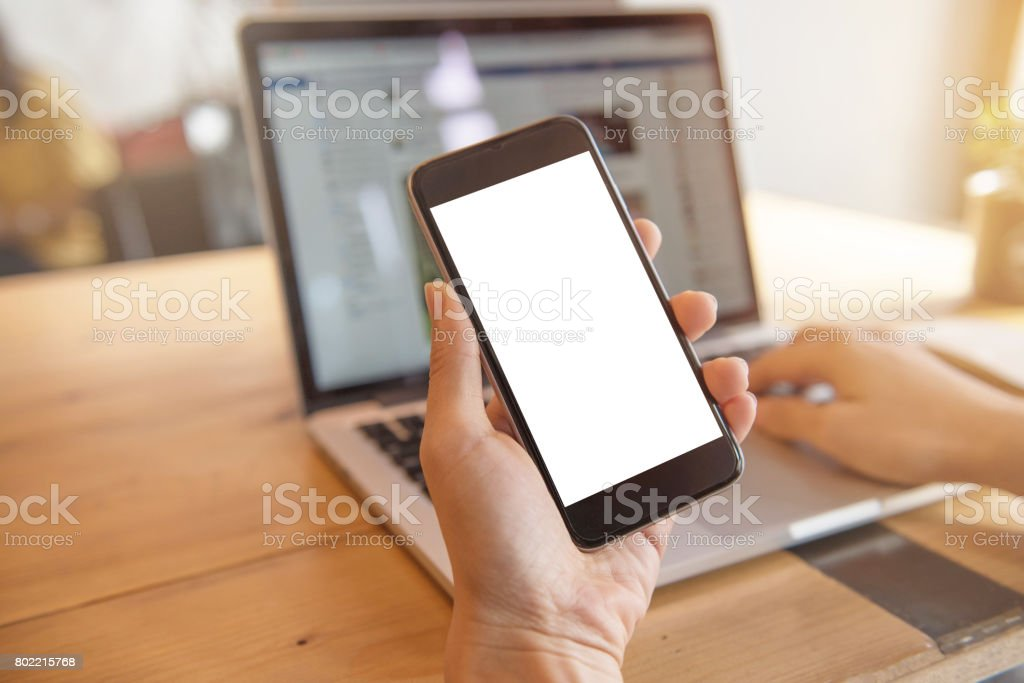 Woman holding smart phone while using laptop background stock photo