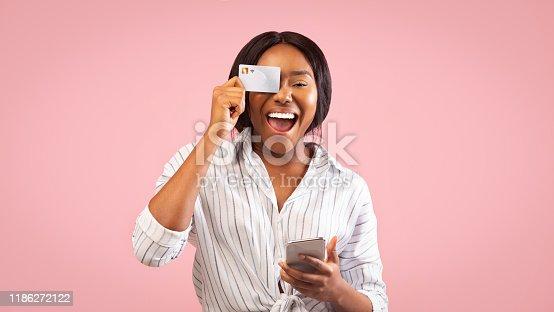 861940002 istock photo Woman Holding Smartphone And Credit Card Having Fun In Studio 1186272122