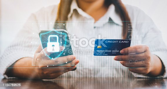 istock Woman holding smartphone and credit card with padlock icon on digital display cyber security internet and networking, Concepts online shopping for protection. 1154789525