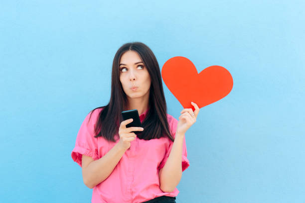Woman Holding Smartphone Finding Internet Love Online Girl using matrimonial website services on her phone date stock pictures, royalty-free photos & images