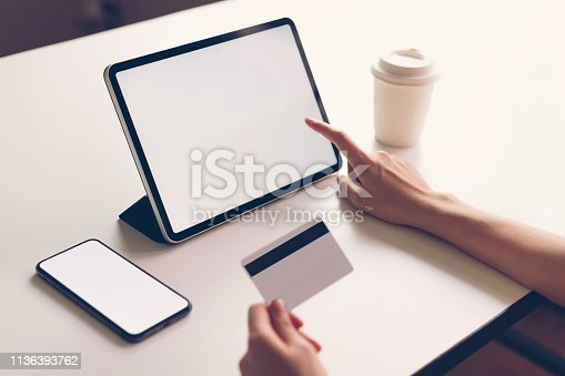 861940002 istock photo Woman holding smartphone mock up of blank screen and credit card on the table. Concepts online shopping for convenience. 1136393762