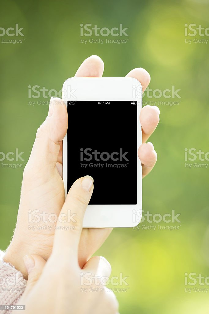 Woman holding smartphone Woman holding smartphone in hands against green spring background Adult Stock Photo