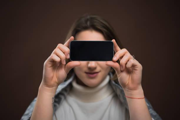 vrouw bedrijf smartphone - verduisterd gezicht stockfoto's en -beelden