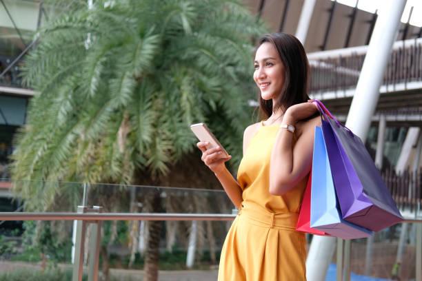 Frau hält Smartphone & Einkaufstaschen. Konsum-Lifestyle in Mall – Foto