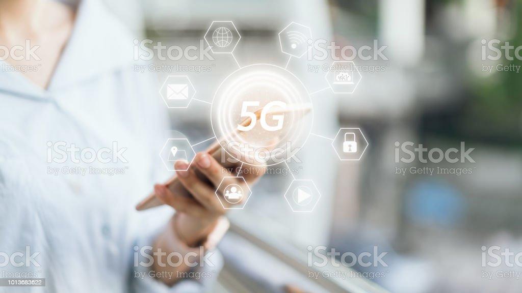 Femme tenant le smartphone à l'icône de l'écran 5G. Concept d'avenir et tendances internet pour faciliter l'accès à l'information. - Photo