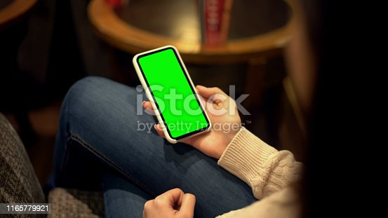 Woman holding smartphone with green screen, place for ad, alpha channel template