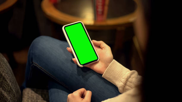 frau hält smartphone mit grünem bildschirm, ort für anzeige, alpha-kanal-vorlage - planner inserts stock-fotos und bilder